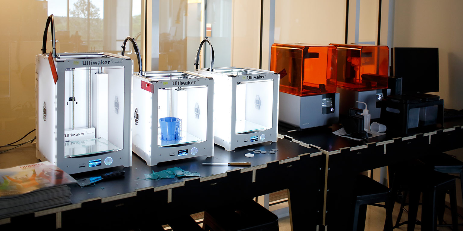 Five 3D printers lined up in a row on a table next to a lab desktop computer