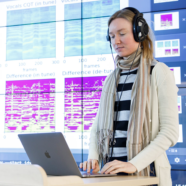 Student Sanna Wager listens to music and interacts with a visualization in the Visualization Lab.